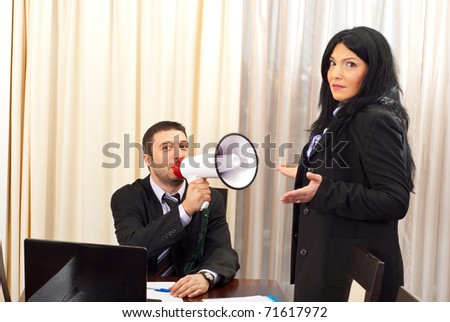 Two business people with megaphone in an office - stock photo