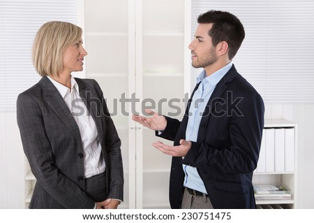 Two business people working in a team talking together in the office.