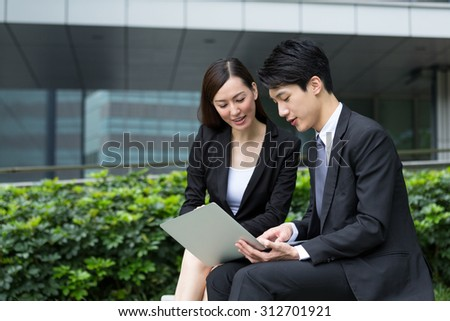 Two business people working together at outdoor - stock photo
