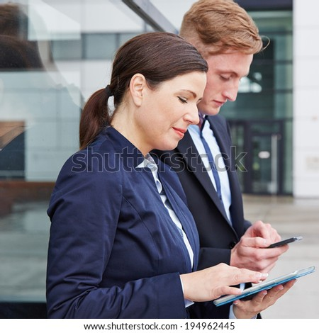 Two business people working with smartphone and tablet PC in front of their office - stock photo