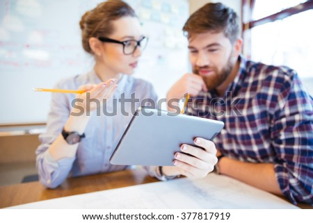 Two business people working with tablet computer in office. Focus on tablet computer - stock photo