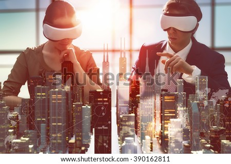 two business persons are developing a project using virtual reality goggles. the concept of technologies of the future - stock photo