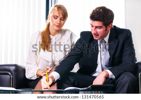 two business persons are sitting and discussing on leather sofa at office