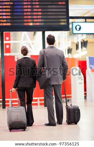 two business travellers looking at airport information board