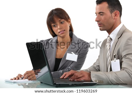 Two business visitors working with laptop - stock photo