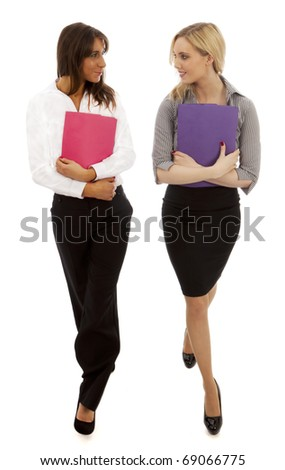 two business woemn walking both holding document files - stock photo