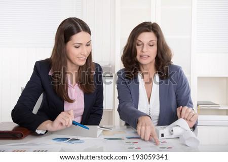 Two business woman analyzing balance sheet. - stock photo