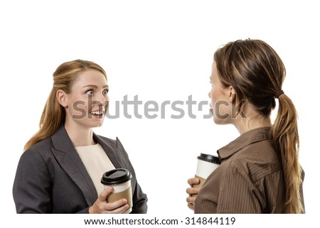 Two business woman chatting and enjoying a gossip over a coffee together - stock photo
