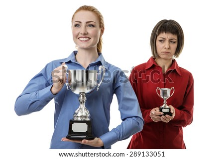 two business woman holding up a trophy, one is holding a large one where the other is holding up a smaller one and not looking happy  - stock photo