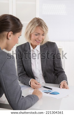 Two business woman sitting at desk: customer and adviser talking together. - stock photo