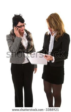 Two business woman standing next to eachother discussions something