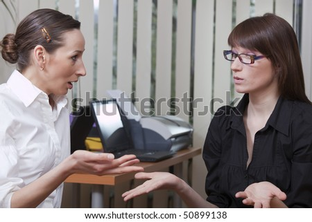 two business women gossip in a office - stock photo
