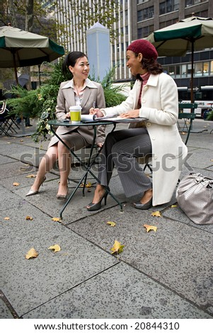 Two business women having a casual meeting in the city. - stock photo