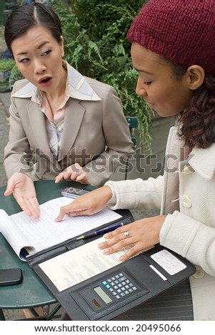 Two business women having a casual meeting in the city.  Shallow depth of field. - stock photo