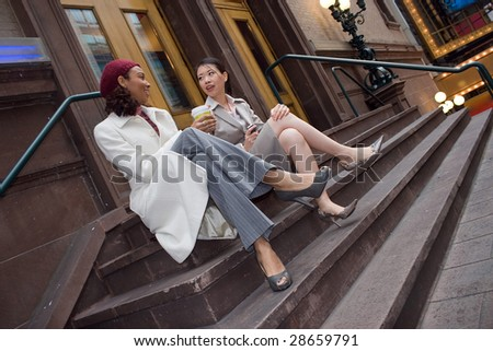Two business women having a casual meeting or discussion in the city. - stock photo