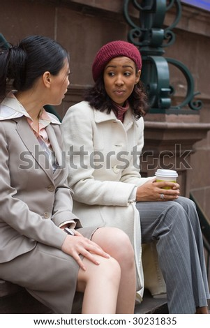 Two business women having a casual meeting or discussion in the city. Shallow depth of field. - stock photo