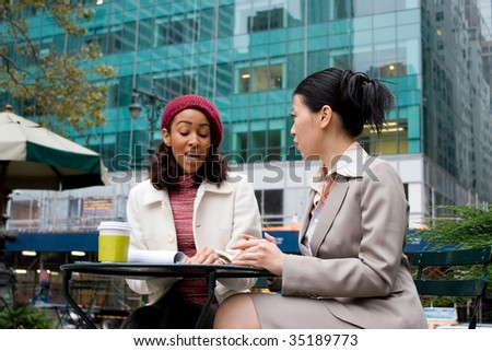 Two business women having a casual meeting or discussion in the city. Shallow depth of field, with focus on the woman to the right. - stock photo
