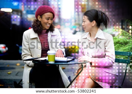 Two business women having a casual meeting or discussion in the city with an abstract glowing halftone circles effect. - stock photo