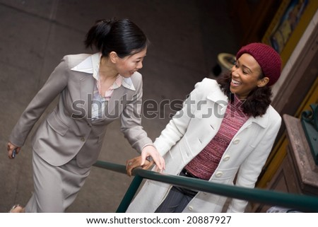 Two business women having a casual meeting or discussion while walking in the city. - stock photo