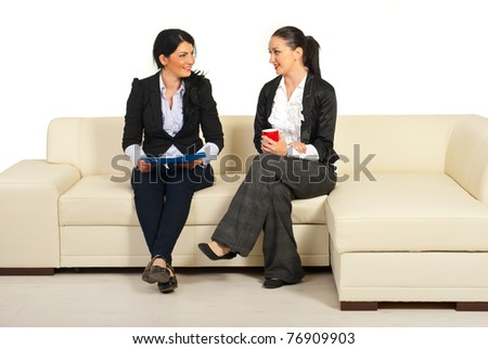 Two business women having conversation and sitting on couch in office