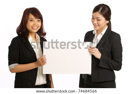 Two business women holding a sign - stock photo