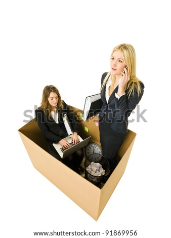 Two Business women in a very small Cardboard office isolated on white background - stock photo