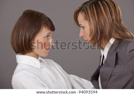 Two business women in conflict over grey background