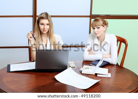 Two business women interacting together at the office. - stock photo