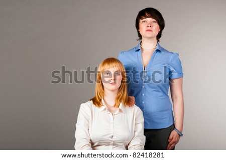 two business women, one is sitting on chair, another is standing nearby