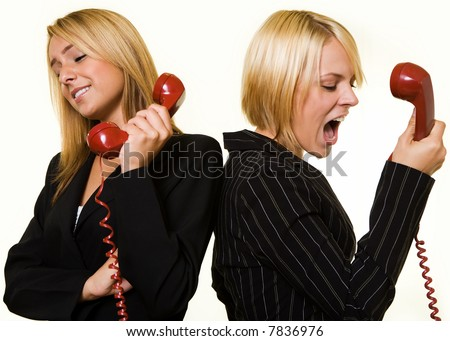 Two business women one yelling into the receiver the other holding the phone away from ear to show a loud argument