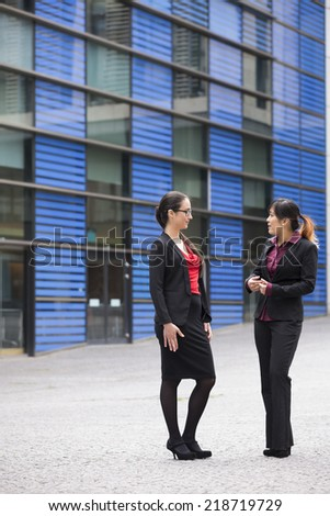 Two business women standing outside talking to each other. - stock photo