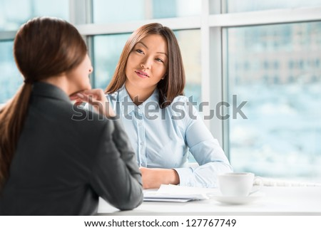 Two business women talking and signing contract at office - stock photo