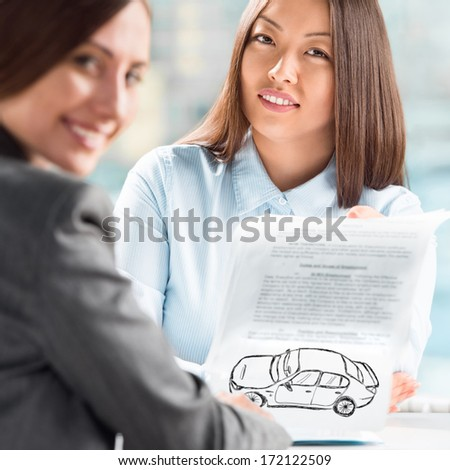 Two business women talking and signing credit or insurance contract at office - stock photo