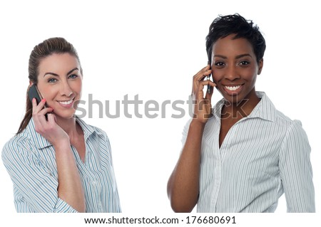 Two business women talking through mobile phone