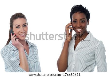 Two business women talking through mobile phone - stock photo