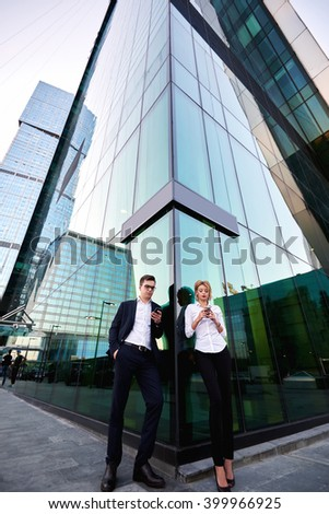 Two business worker are searching needed for briefing information on web page via mobile phones, while are standing outdoor against tall skyscraper building background with copy space for your content - stock photo