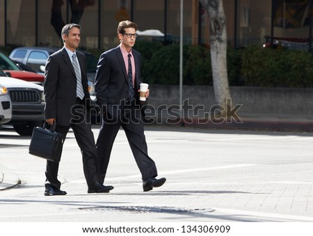 Two Businessman Chatting Whilst Crossing Street