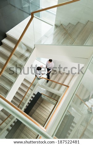Two businessman discussing something on the staircase, view from above - stock photo