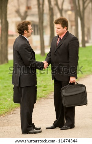 Two businessman handshake outdoors scene
