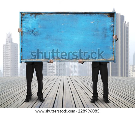 two businessman hold old blue empty wooden noticeboard stand on wooden floor with skyscraper cityscape background - stock photo