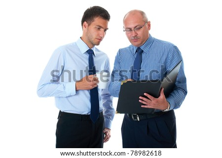 two businessman in blue shirts check and discuss their documents, break time, one hold tea cup, mug, isolated on white - stock photo