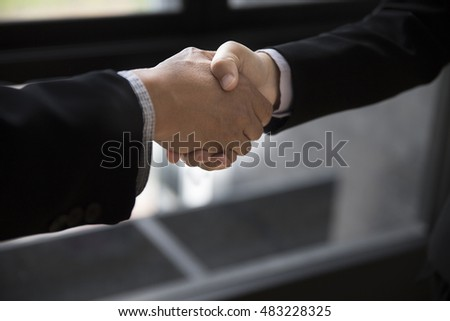 two businessman in suit shaking hands beside window - business teamwork, cooperation concept