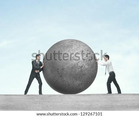 two businessman pushing concrete ball - stock photo