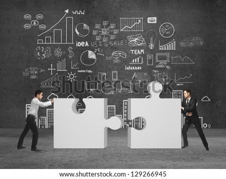 two businessman puts puzzle on concrete room - stock photo