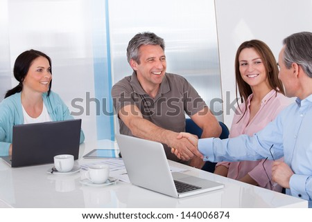 Two Businessman Shaking Hand In Front Of Colleague In Office