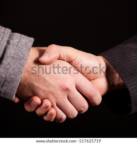 Two businessman shaking hands over black