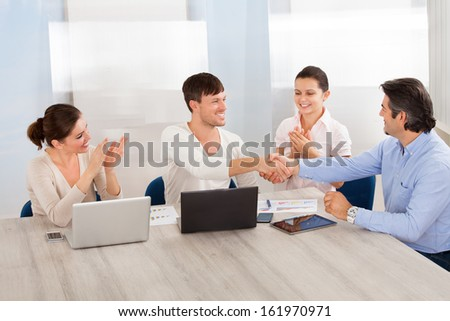 Two Businessman Shaking Hands With His Partner In Front Of Colleagues At Office - stock photo