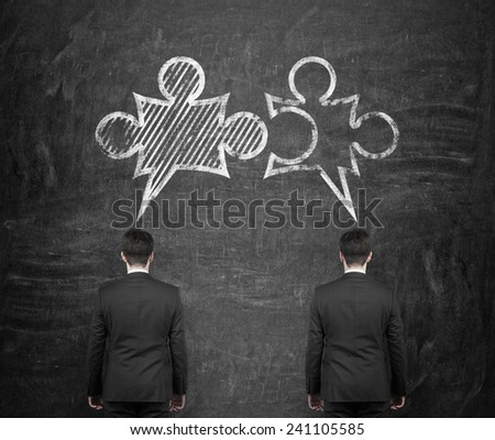 two businessman thinkig with drawing puzzle over head - stock photo