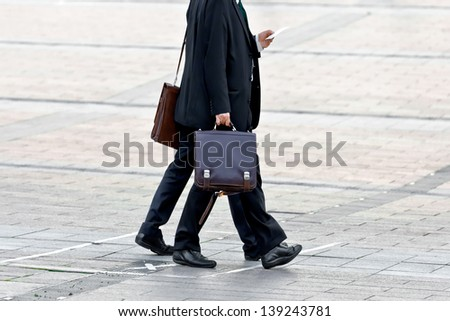 Two businessman walking conversing. Agreement. Urban scene. - stock photo