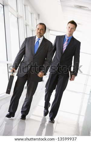 Two businessman walking through office lobby - stock photo